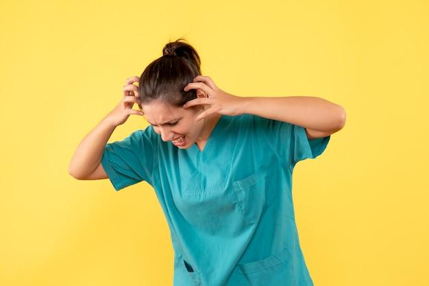 Вид спереди женщина-врач в медицинской рубашке на желтом фоне