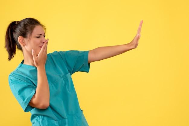 노란색 배경에 의료 셔츠에 전면보기 여성 의사