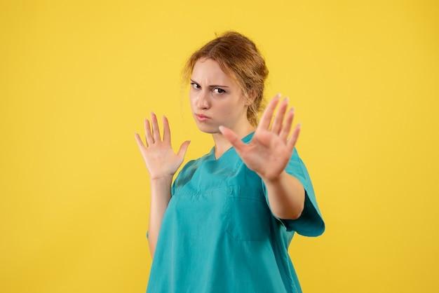 Вид спереди женщина-врач в медицинской рубашке на желтом столе, больничный медик, медсестра, медсестра, цвет медицины covid-19