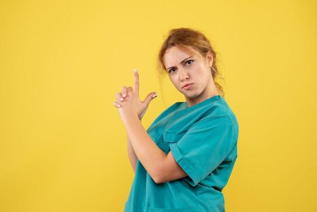 Вид спереди женщина-врач в медицинской рубашке позирует, медсестра больницы covid-19, цветная медицина