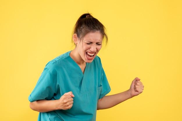 黄色の背景で喜んで医療シャツの正面の女性医師