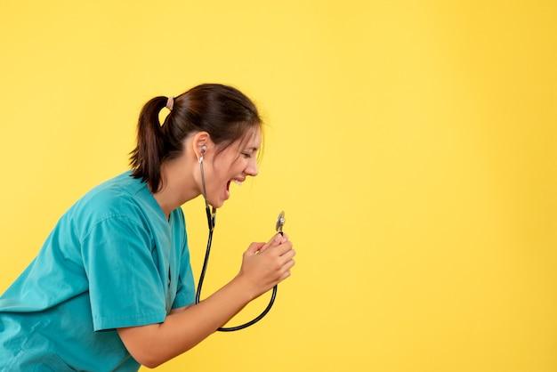 Вид спереди женщина-врач в медицинской рубашке кричит на стетоскоп на желтом фоне