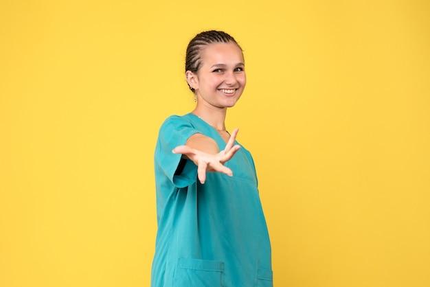 Вид спереди женщина-врач в медицинской рубашке улыбается, цветная больничная медсестра, вирус здоровья covid-19