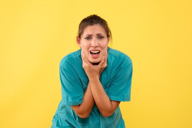 黄色の背景に歯痛に苦しんでいる医療シャツの正面図の女性医師