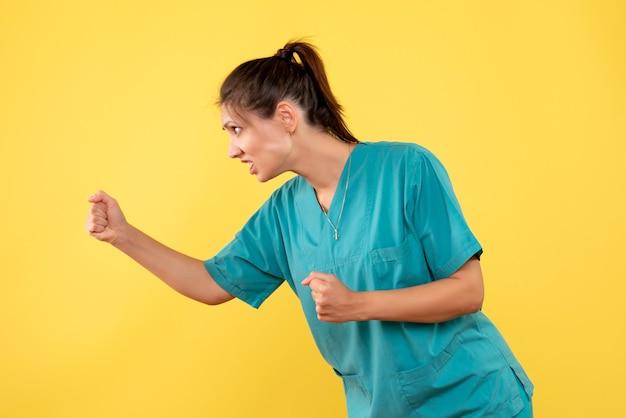 노란색 배경에 위협 의료 셔츠에 전면보기 여성 의사