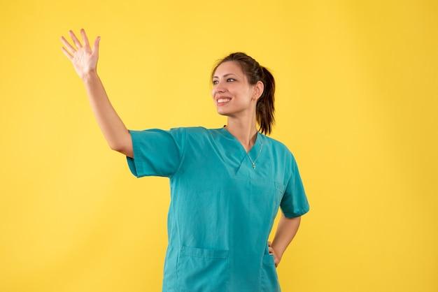 黄色の背景に笑顔で手を振っている医療シャツの正面図