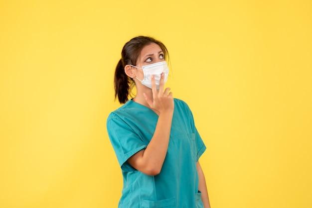의료 셔츠와 노란색 배경에 멸균 마스크 전면보기 여성 의사