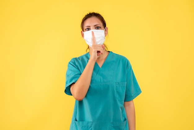 医療シャツと黄色の背景に滅菌マスクで正面図の女性医師