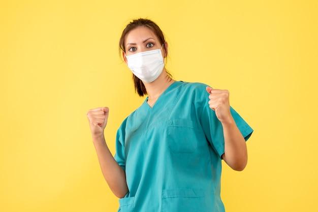 노란색 배경에 기뻐하는 멸균 마스크와 의료 셔츠에 전면보기 여성 의사
