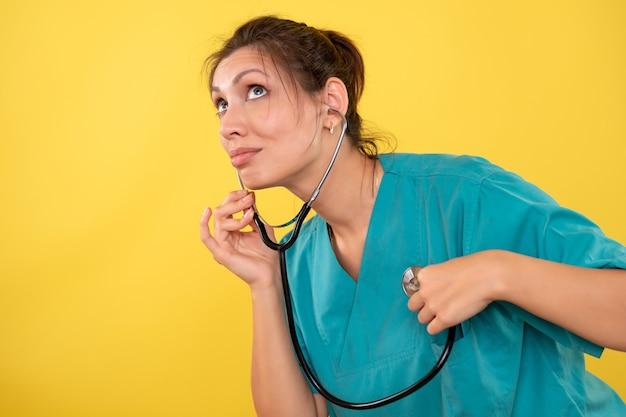 Вид спереди женщина-врач в медицинской рубашке со стетоскопом на желтом фоне