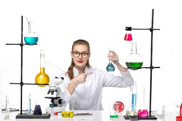 흰색 배경 바이러스 covid 유행성 코로나 바이러스에 대한 솔루션 테이블 앞에 앉아 의료 소송에서 전면보기 여성 의사