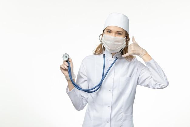 Вид спереди женщина-врач в медицинском костюме в маске из-за коронавируса, держащая стетоскоп на белом столе, пандемия вируса covid- болезнь