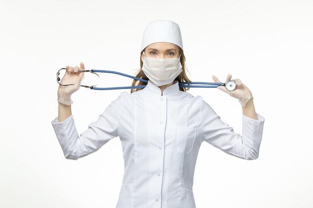 Вид спереди женщина-врач в медицинском костюме в маске из-за коронавируса, держащая стетоскоп на белой стене, вирус пандемии covid-