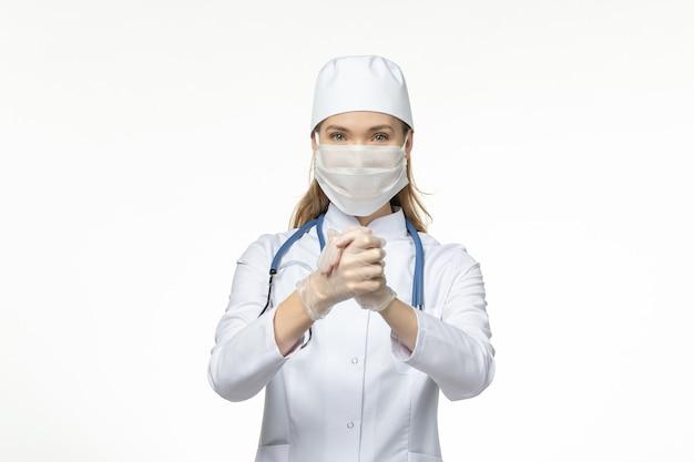밝은 흰색 책상에 코로나 바이러스로 인해 마스크를 쓰고 의료 복을 입은 여성 의사 전면보기 질병 covid- pandemic virus disease