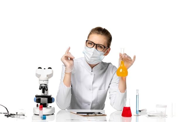 Вид спереди женщина-врач в медицинском костюме в маске из-за covid, работающего с растворами на белом столе