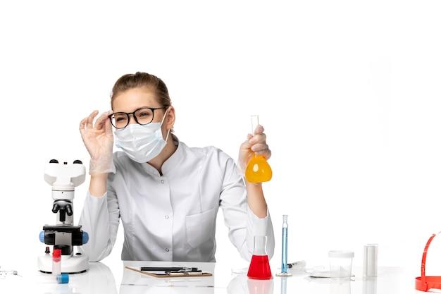 Вид спереди женщина-врач в медицинском костюме в маске из-за covid, работающего с решениями по вирусу болезни белого пола, пандемическому здоровью covid-
