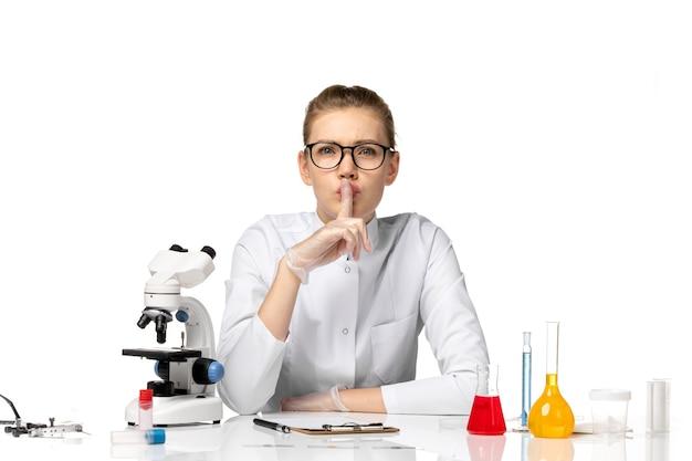 Вид спереди женщина-врач в медицинском костюме с перчатками, сидящая с растворами на белом пространстве