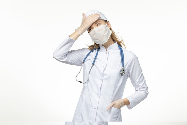 白壁病パンデミックコビッドウイルスのコロナウイルスによるマスクと手袋を着用した医療スーツの正面図の女性医師
