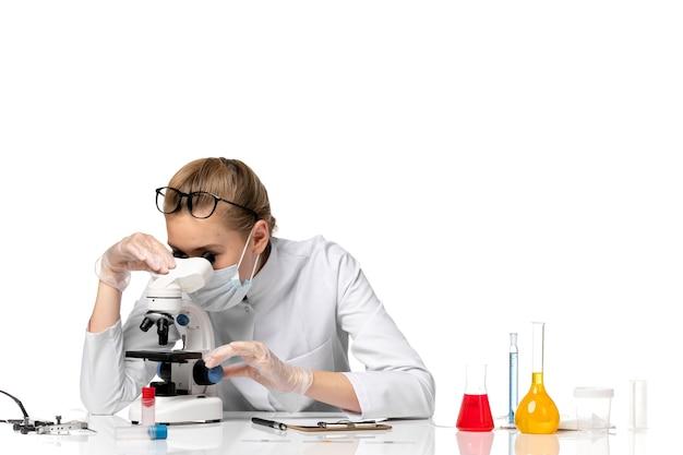 밝은 공백에 현미경을 사용하여 covid로 인해 마스크가있는 의료 소송에서 전면보기 여성 의사