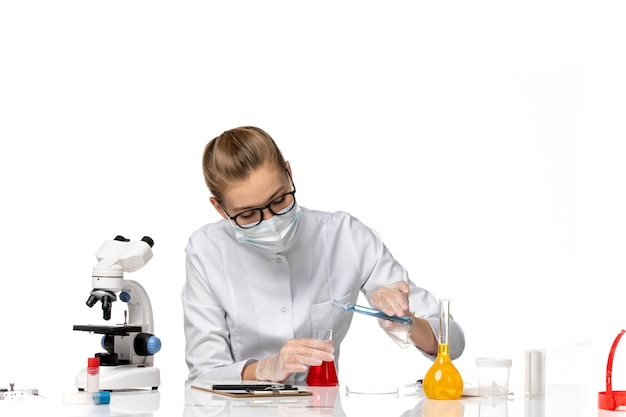 明るい白いスペースでソリューションを使用してcovid作業のため、マスク付きの医療スーツの正面図の女性医師