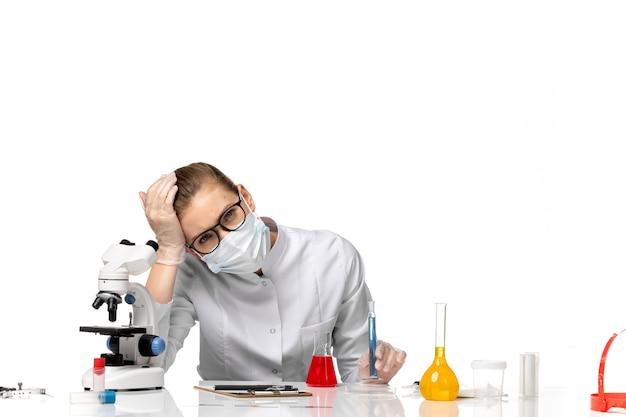 밝은 흰색 공간에서 솔루션으로 작업하는 covid로 인해 마스크가있는 의료 소송에서 전면보기 여성 의사