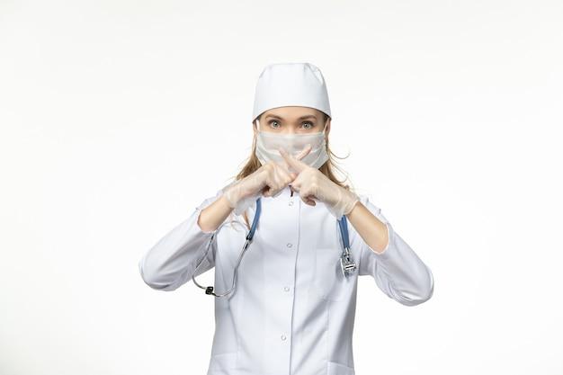 흰 벽에 코로나 바이러스로 인해 멸균 마스크가있는 의료 소송에서 전면보기 여성 의사 질병 유행성 covid-
