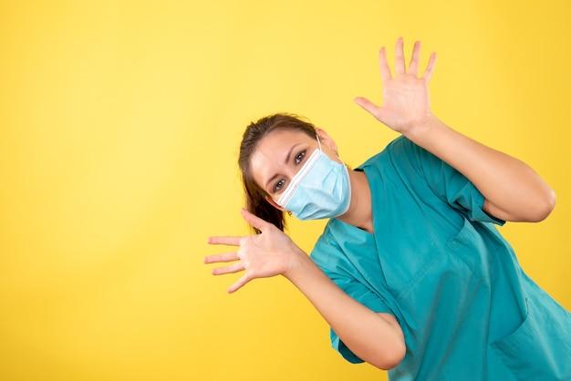 Вид спереди женщина-врач в защитной маске на желтом фоне