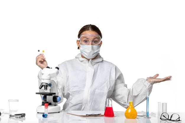 防護服を着た正面図の女性医師と白い背景の薬の健康パンデミックウイルスコロナウイルスの小さなサンプルを保持しているマスク
