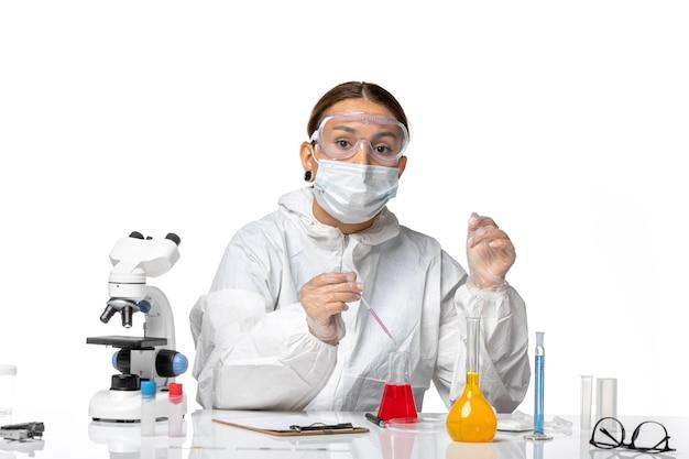 防護服を着た正面図の女性医師と、明るい白の背景にソリューションを扱うマスクを使用したcovidパンデミックウイルスコロナウイルス