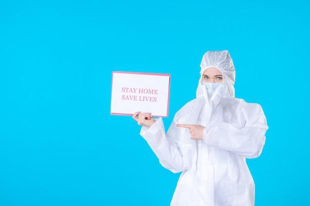 外出禁止令を保持している防護服の正面図女性医師は青い背景で命を救う健康科学covid分離パンデミックウイルス医療