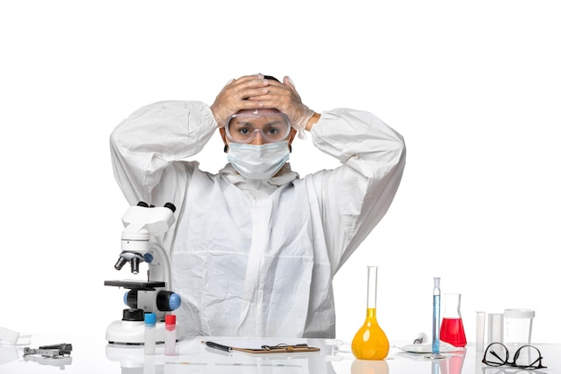 특별 한 옷을 입고 흰색 책상에 마스크를 쓰고 전면보기 여성 의사 covid- pandemic coronavirus virus health