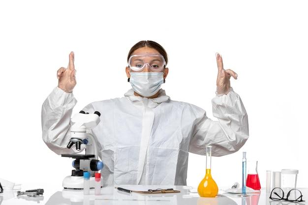 특수 양복과 흰색 배경에 솔루션과 함께 앉아 마스크를 쓰고 전면보기 여성 의사 covid-virus pandemic coronavirus