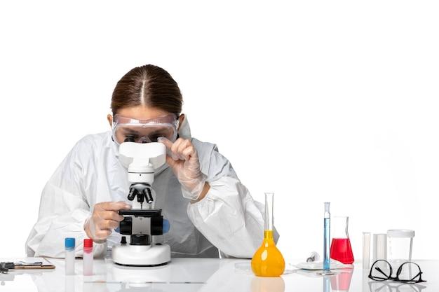 특수 양복과 흰색 책상에 현미경으로 작업하는 마스크 착용 전면보기 여성 의사 covid virus pandemic coronavirus