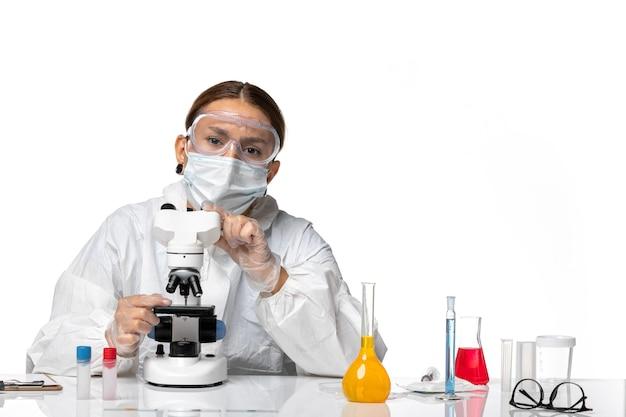 특수 양복과 흰색 배경에 현미경으로 작업하는 마스크를 쓰고 전면보기 여성 의사 covid 유행성 코로나 바이러스 바이러스