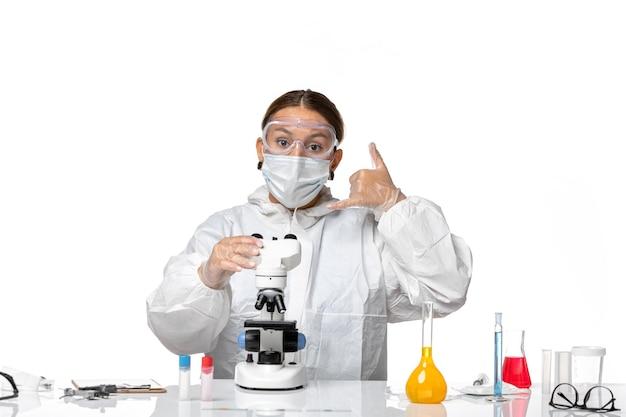 Вид спереди женщина-врач в специальном костюме и в маске, работающая с микроскопом на белом фоне, пандемия коронавируса вируса ковид
