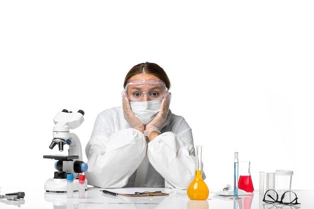 特別なスーツを着て、白い机での集中的な作業にうんざりしているマスクを持った正面図の女性医師