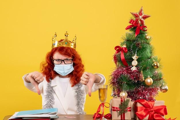 Вид спереди женщина-врач в стерильной маске вокруг рождественских подарков