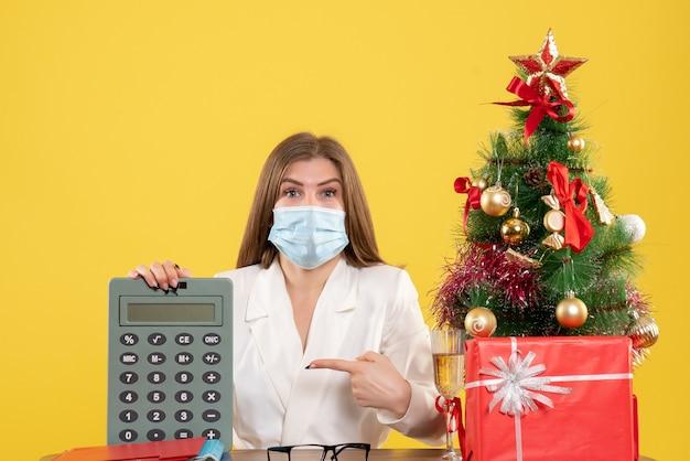 計算機を保持している滅菌マスクの正面図の女性医師