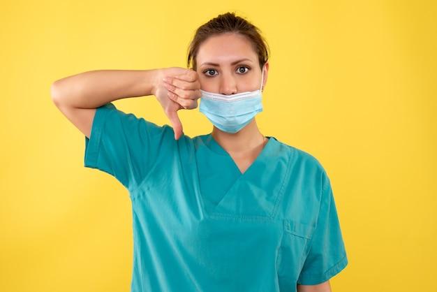 黄色の背景に滅菌マスクの正面図女性医師