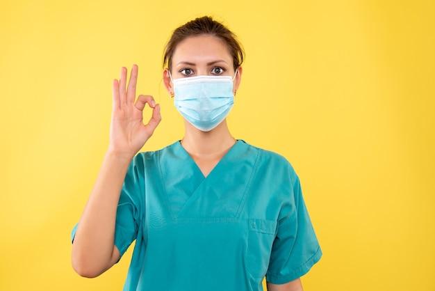 노란색 배경에 멸균 마스크 전면보기 여성 의사