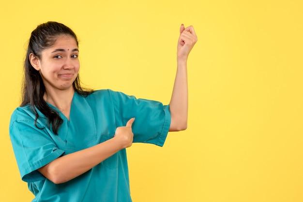 서 그녀의 팔 근육을 가리키는 제복을 입은 전면보기 여성 의사