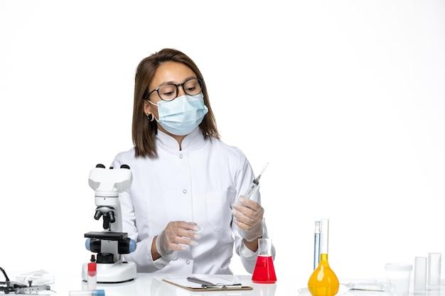 Вид спереди женщина-врач в белом медицинском костюме и маске из-за коронавируса, держащего инъекцию на белом пространстве
