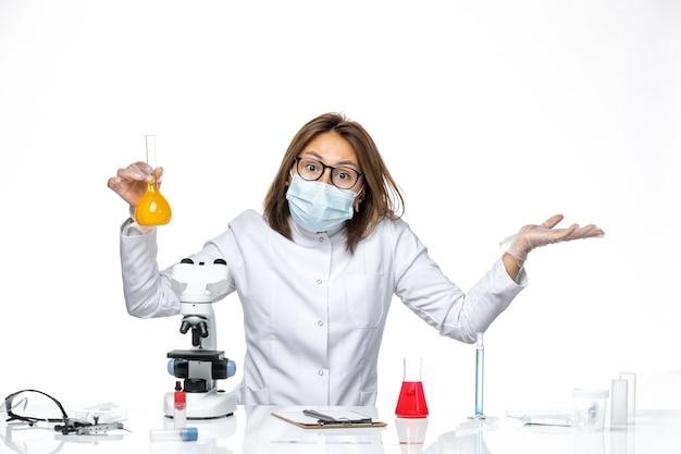 흰색 책상에 솔루션 작업 코로나 바이러스로 인해 흰색 의료 양복과 마스크의 전면보기 여성 의사