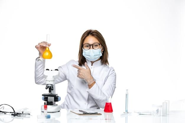 明るい白いスペースでソリューションを処理しているコロナウイルスによる白い医療スーツとマスクの正面図の女性医師