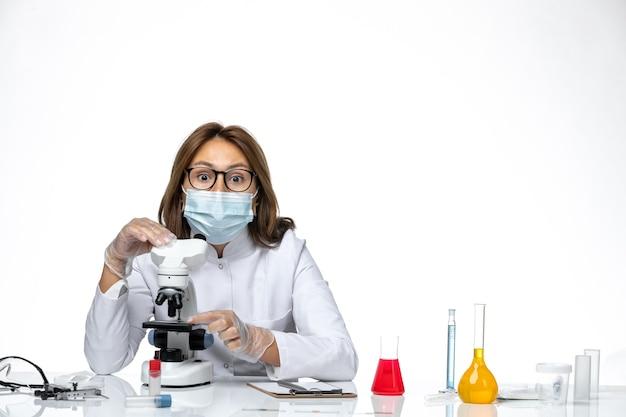 밝은 공백에 현미경을 사용하여 covid로 인해 흰색 의료 양복과 마스크의 전면보기 여성 의사