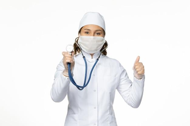 흰색 의료 양복과 흰 벽에 청진기를 사용하는 마스크의 전면보기 여성 의사 pandemy 바이러스 질병 약