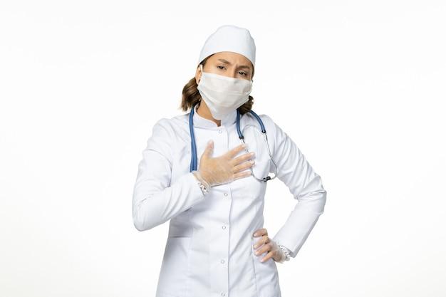 白い医療スーツと白い机の上のコロナウイルスによるマスクを持った正面図の女性医師ウイルス病パンデミックコビッド