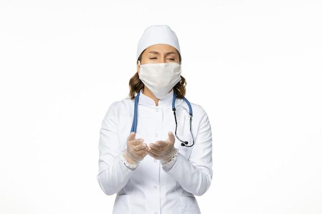 白い医療スーツを着た正面図の女性医師と白い床のウイルス病パンデミックコビッドのコロナウイルスによるマスク