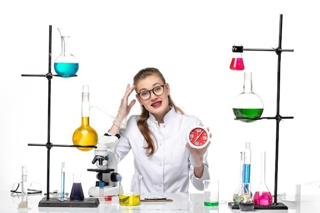 明るい白い机の上の時計を保持している白い医療スーツの正面図女性医師ウイルス化学パンデミックcovid