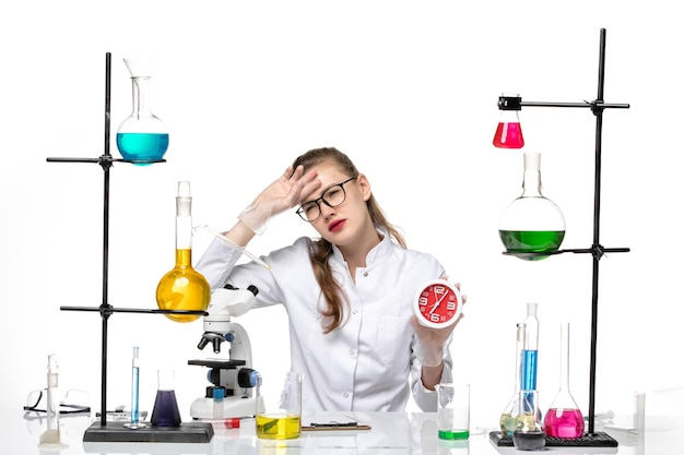 白い机の上の時計を保持している白い医療スーツの正面図女性医師ウイルス化学パンデミックcovid
